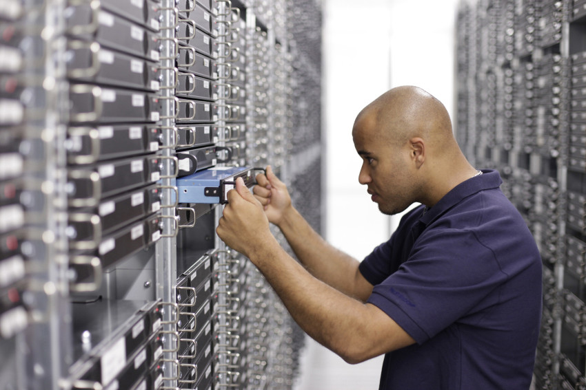 Wartungsarbeiten im STRATO Rechenzentrum erfolgreich beendet: Ein STRATO Mitarbeiter hebt einen Server zurück in ein Rack.